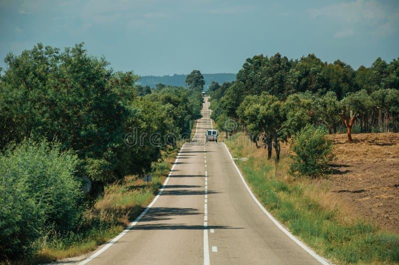 Δρόμος με το μόνο αυτοκίνητο μέσω του αγροτικών τοπίου και των δέντρων στοκ φωτογραφία με δικαίωμα ελεύθερης χρήσης