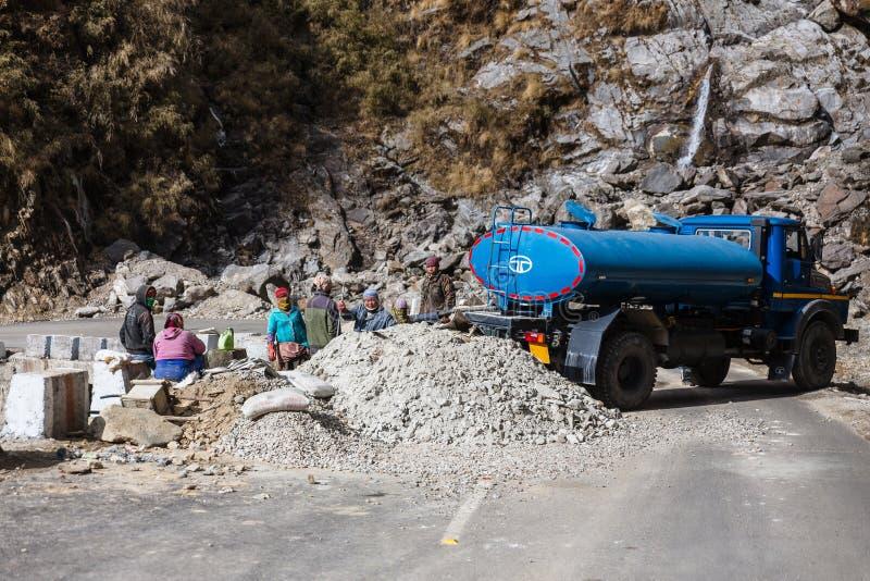 Δρόμος που εμποδίζεται με τους εργαζομένους και το μπλε φορτηγό για τον καθορισμό του δρόμου το χειμώνα κοντά στον τρόπο στη λίμν στοκ φωτογραφία με δικαίωμα ελεύθερης χρήσης