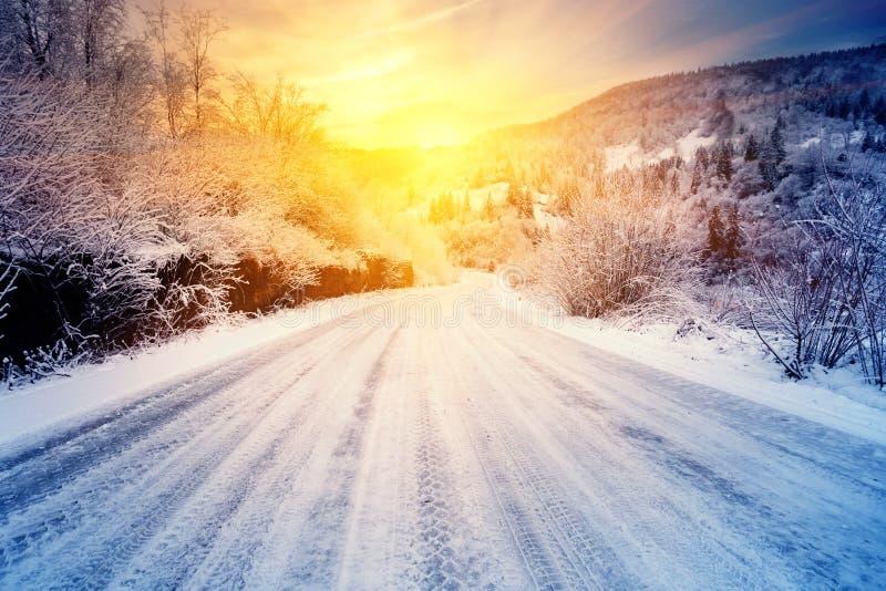 Δρόμος στο ηλιοβασίλεμα στα χειμερινά βουνά στοκ φωτογραφίες