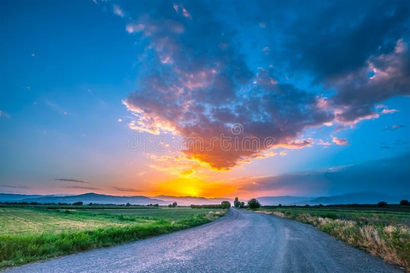 Δρόμος στο λιβάδι με τον όμορφο ουρανό ηλιοβασιλέματος στοκ εικόνα