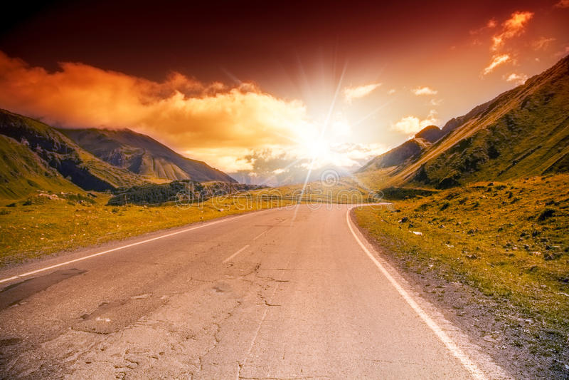 Δρόμος στο τοπίο βουνών με το φωτεινό ηλιοβασίλεμα στοκ φωτογραφίες