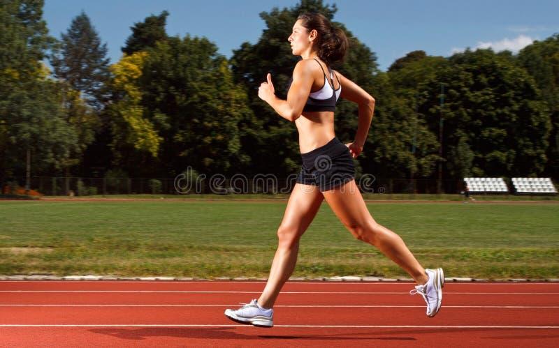 Δυναμική εικόνα μιας νέας γυναίκας που τρέχει σε μια διαδρομή στοκ εικόνες με δικαίωμα ελεύθερης χρήσης