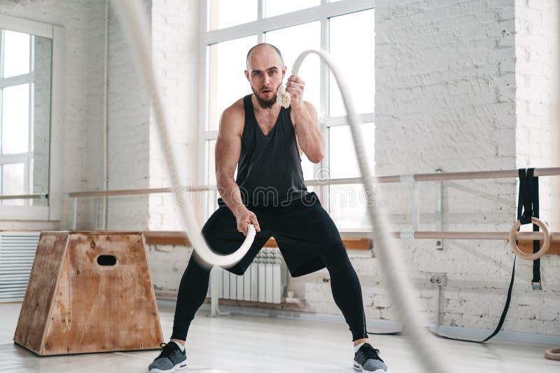 Δυναμικός πυροβολισμός του ισχυρού ατόμου workout με τα σχοινιά μάχης στην ελαφριά γυμναστική στοκ εικόνα