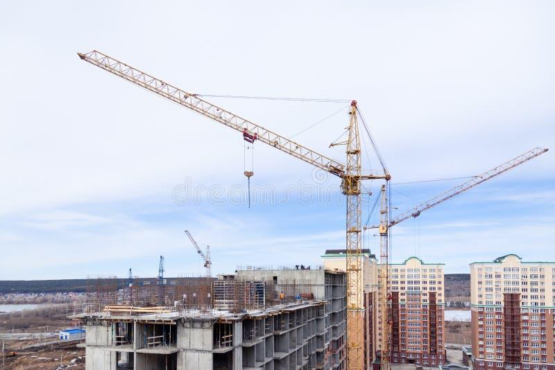 Δυνατός γερανός ανύψωσης πολυόροφων κτιρίων και μεγάλο εργοτάξιο οικοδομής οικοδόμησης με τους γερανούς με το μακρύ κίτρινο βέλος στοκ φωτογραφία με δικαίωμα ελεύθερης χρήσης