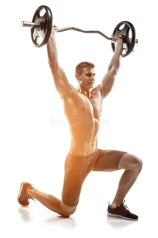 Δυνατό άτομο που στέκεται στο γόνατο, που κρατά barbell πέρα από το κεφάλι του στοκ φωτογραφία