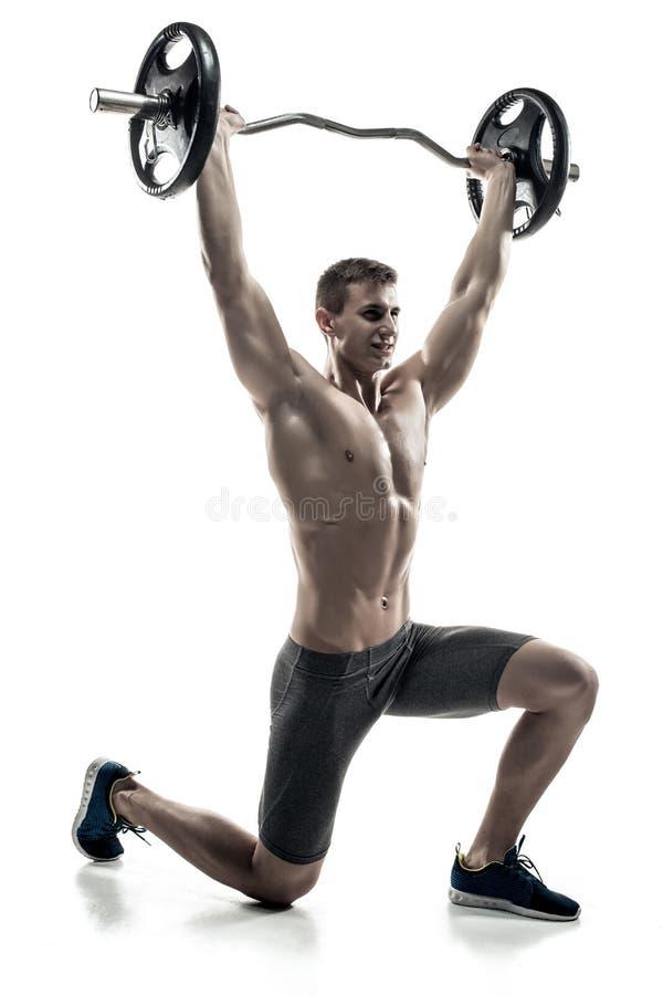 Δυνατό άτομο που στέκεται στο γόνατο, που κρατά barbell πέρα από το κεφάλι του στοκ εικόνες
