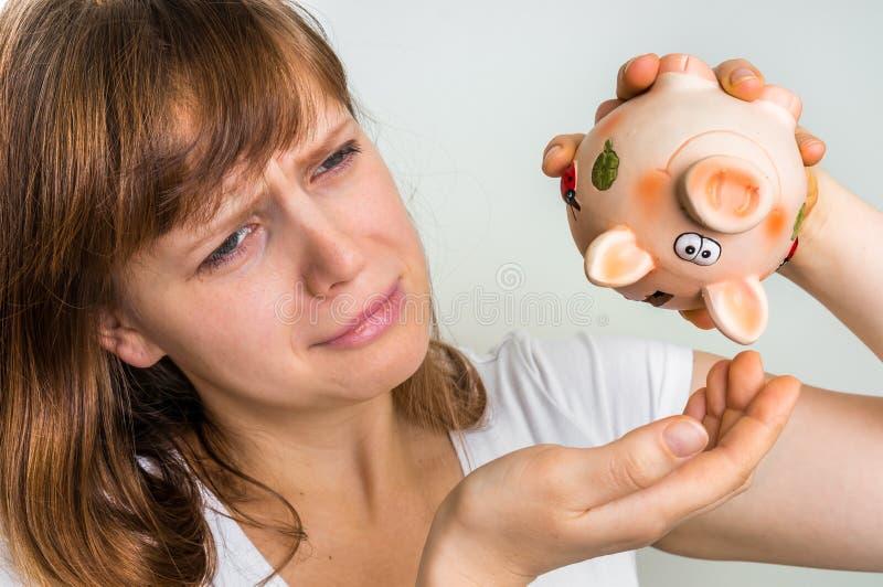 Δυστυχισμένη γυναίκα που τινάζει μια κενή piggy τράπεζα στοκ φωτογραφία με δικαίωμα ελεύθερης χρήσης