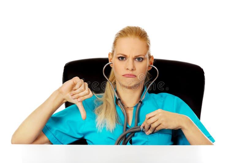 Δυστυχισμένη θηλυκή συνεδρίαση γιατρών ή νοσοκόμων πίσω από το γραφείο με το στηθοσκόπιο και την παρουσίαση αντίχειρα κάτω στοκ εικόνες με δικαίωμα ελεύθερης χρήσης