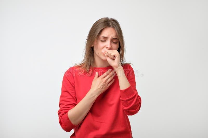 Δυστυχισμένη καυκάσια γυναίκα στο κόκκινο pulover που πάσχει από τον πόνο λαιμού στο σπίτι στοκ εικόνες
