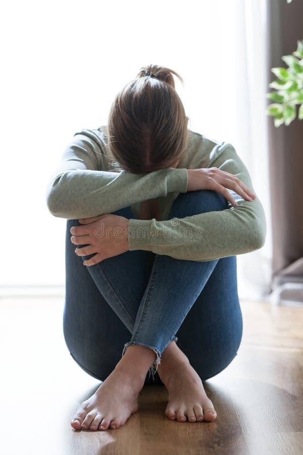 Δυστυχισμένη μόνη και καταθλιπτική νέα γυναίκα που κρύβει το πρόσωπό της μεταξύ των ποδιών στο σπίτι στοκ εικόνες