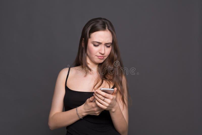 Δυστυχισμένη νέα γυναίκα που χρησιμοποιεί το πορτρέτο smartphone στοκ φωτογραφίες