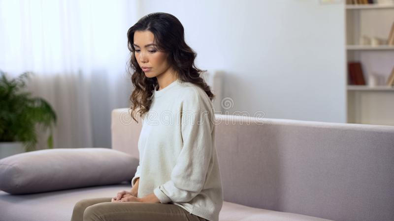 Δυστυχισμένη νέα συνεδρίαση γυναικών στον καναπέ μόνο, λυπημένος για το χωρισμό με το φίλο στοκ εικόνες