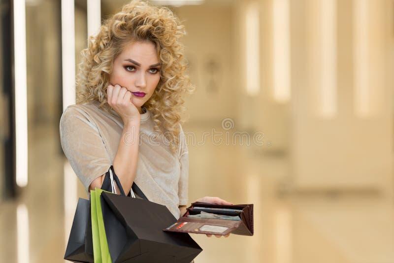 Δυστυχισμένη πτωχεύσασα γυναίκα με το κενό πορτοφόλι Η νέα γυναίκα εμφανίζει κενό πορτοφόλι της στοκ εικόνα με δικαίωμα ελεύθερης χρήσης