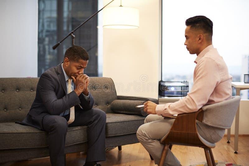 Δυστυχισμένη συνεδρίαση επιχειρηματιών στη συνεδρίαση των καναπέδων με τον αρσενικό σύμβουλο στην αρχή στοκ εικόνα με δικαίωμα ελεύθερης χρήσης