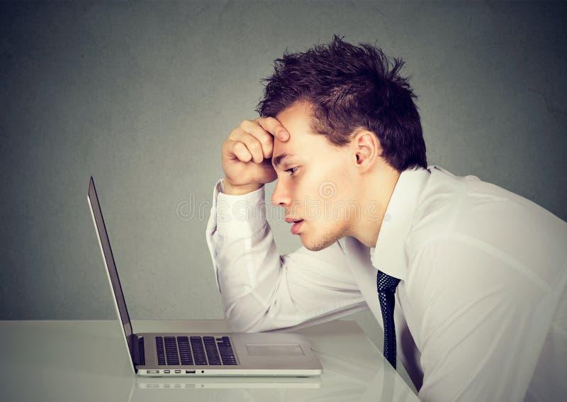 Δυστυχισμένη τονισμένη λυπημένη συνεδρίαση ατόμων στο γραφείο μπροστά από το lap-top του στοκ φωτογραφία με δικαίωμα ελεύθερης χρήσης