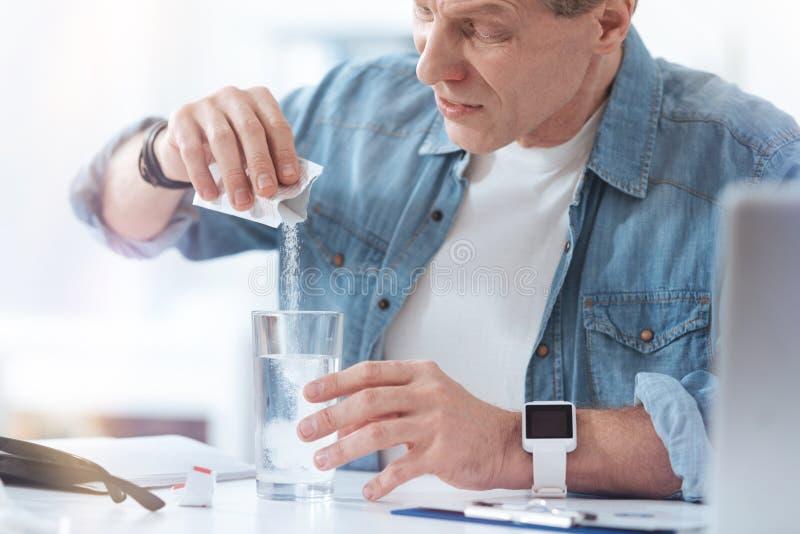 Δυστυχισμένος άρρωστος άνδρας που προετοιμάζει την ιατρική του στοκ εικόνα με δικαίωμα ελεύθερης χρήσης