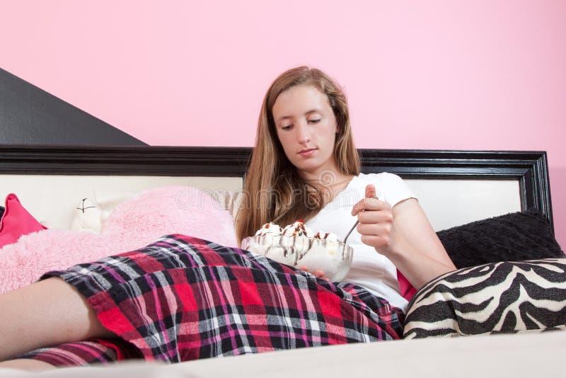 Δυστυχισμένος έφηβος που τρώει μεγάλο sundae παγωτού στο δωμάτιό της στοκ εικόνες