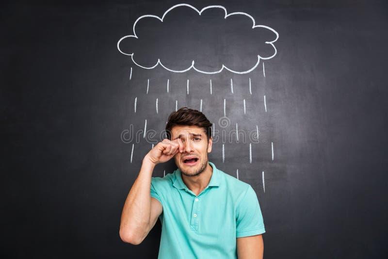 Δυστυχισμένος απογοητευμένος νεαρός άνδρας που φωνάζει κάτω από τη συρμένη βροχή στοκ φωτογραφία