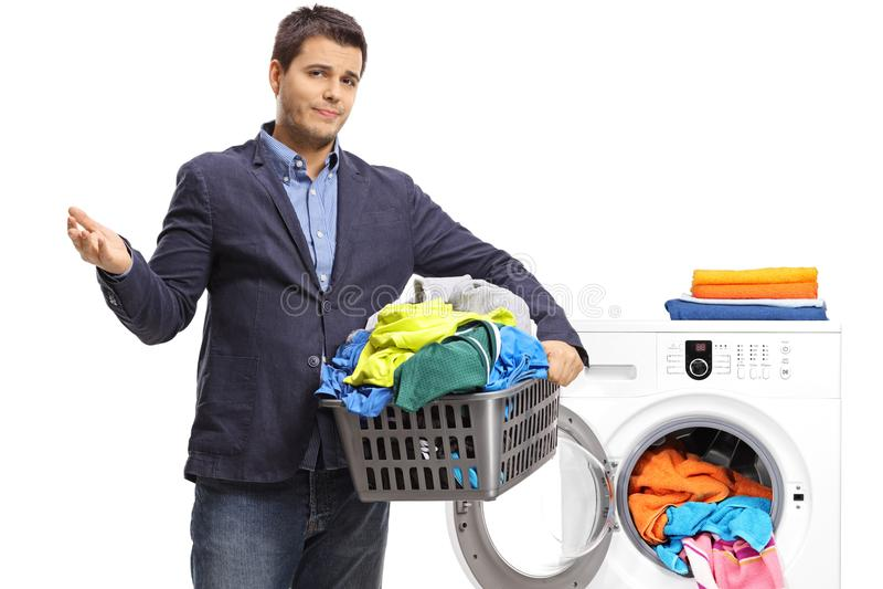 Δυστυχισμένος κομψός τύπος που κρατά ένα καλάθι πλυντηρίων γεμισμένο με τα ενδύματα στοκ φωτογραφίες με δικαίωμα ελεύθερης χρήσης