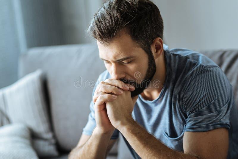 Δυστυχισμένος νεαρός άνδρας που κρατά το πηγούνι του στοκ εικόνες