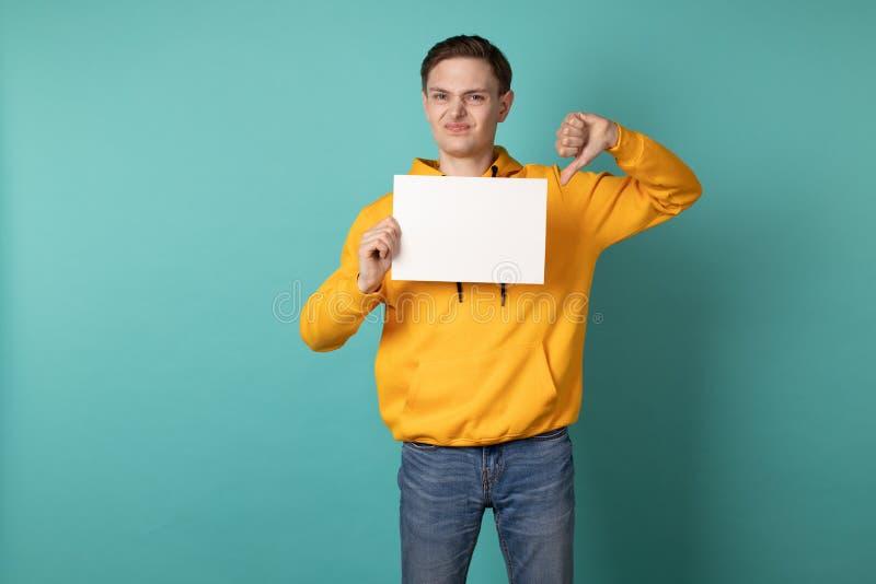 Δυστυχισμένος νεαρός άνδρας στο κίτρινο hoodie που απομονώνεται πέρα από το μπλε υπόβαθρο στοκ εικόνες