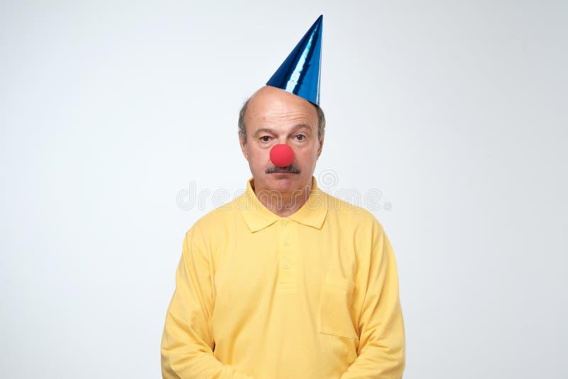 Δυστυχισμένος τύπος γενεθλίων στην κίτρινη μπλούζα και την κόκκινη μύτη κλόουν που στέκονται στο άσπρο υπόβαθρο στοκ φωτογραφία
