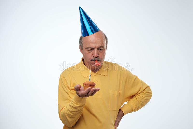 Δυστυχισμένος τύπος γενεθλίων στην κίτρινη μπλούζα και την μπλε ΚΑΠ που στέκονται στο άσπρο κέικ γενεθλίων εκμετάλλευσης υποβάθρο στοκ εικόνα
