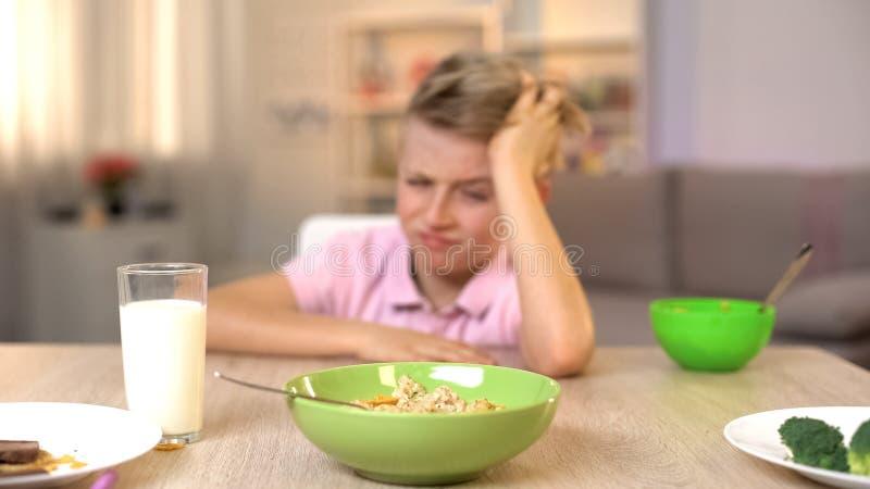 Δυστυχισμένο αγόρι που φαίνεται oatmeal με την αποστροφή, unappetizing τρόφιμα, υγιές πρόγευμα στοκ φωτογραφία με δικαίωμα ελεύθερης χρήσης
