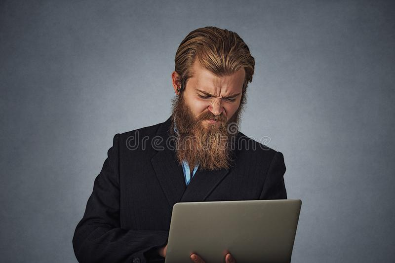 Δυστυχισμένο αρσενικό συνοφρύωμα φορητών προσωπικών υπολογιστών εκμετάλλευσης ατόμων στοκ φωτογραφία με δικαίωμα ελεύθερης χρήσης