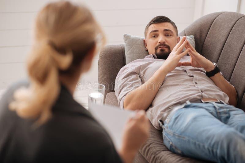 Δυστυχισμένο γενειοφόρο άτομο που εξετάζει τον ψυχολόγο του στοκ φωτογραφία με δικαίωμα ελεύθερης χρήσης