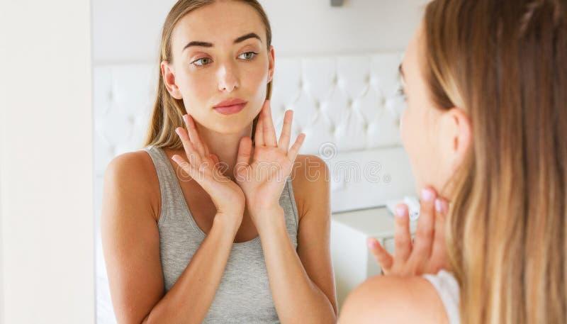 Δυστυχισμένο κορίτσι μπροστά από έναν καθρέφτη που εξετάζει τις ρυτίδες της στοκ εικόνες με δικαίωμα ελεύθερης χρήσης