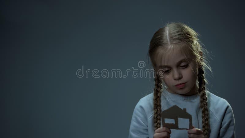 Δυστυχισμένο κορίτσι που εξετάζει το σπίτι εγγράφου, ορφανό παιδί που ονειρεύεται για το σπίτι, θλίψη στοκ εικόνα