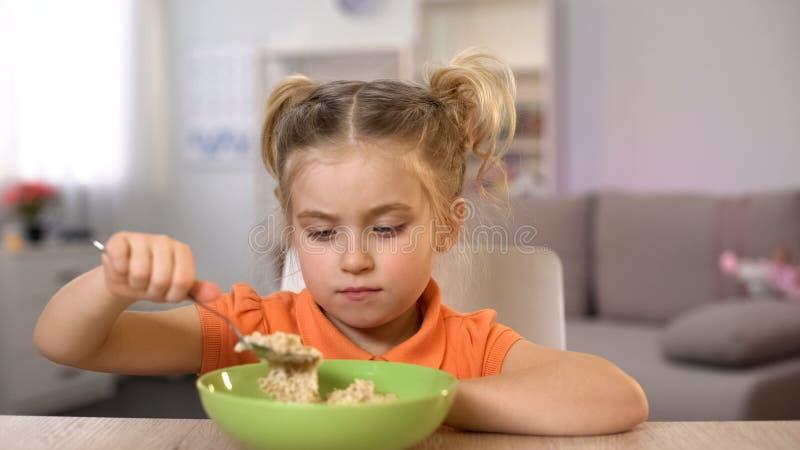 Δυστυχισμένο κορίτσι που εξετάζει oatmeal, υγιής αλλά tasteless διατροφή, να κάνει δίαιτα στοκ φωτογραφίες με δικαίωμα ελεύθερης χρήσης