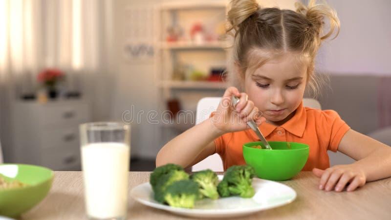 Δυστυχισμένο κορίτσι που τρώει τα υγιή αλλά tasteless τρόφιμα, μπρόκολο που βρίσκονται στον πίνακα, διατροφή στοκ φωτογραφία με δικαίωμα ελεύθερης χρήσης