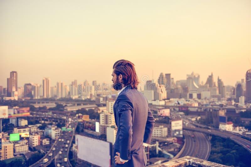 Δυτικός επιχειρηματίας που εξετάζει την πόλη της Μπανγκόκ στο ηλιοβασίλεμα στοκ φωτογραφία με δικαίωμα ελεύθερης χρήσης