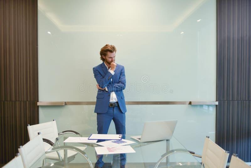 Δυτικός επιχειρηματίας που παρουσιάζει ένα πρόγραμμα για τον κενό πίνακα γυαλιού μέσα στοκ φωτογραφία