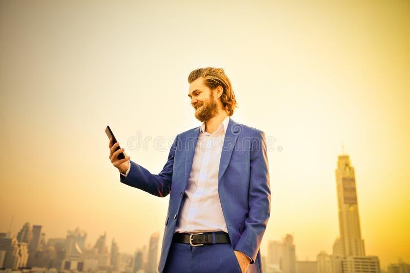 Δυτικός επιχειρηματίας που χρησιμοποιεί ένα τηλέφωνο σε μια στέγη με τη μουτζουρωμένη πόλη στοκ εικόνα με δικαίωμα ελεύθερης χρήσης