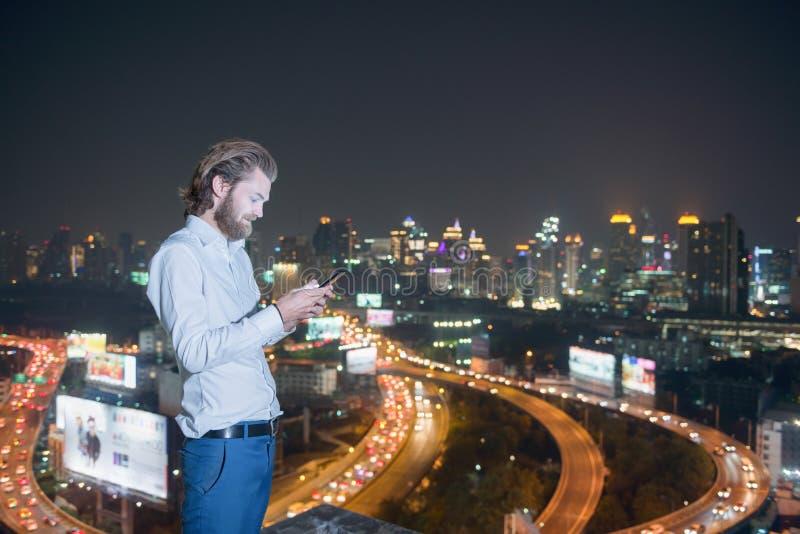 Δυτικός επιχειρηματίας που χρησιμοποιεί το τηλέφωνο με το υπόβαθρο πόλεων, technolog στοκ φωτογραφίες