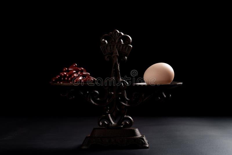 Δωδεκάδες των καψών και ενός αυγού σε μια ισορροπημένη κλίμακα στοκ φωτογραφία με δικαίωμα ελεύθερης χρήσης