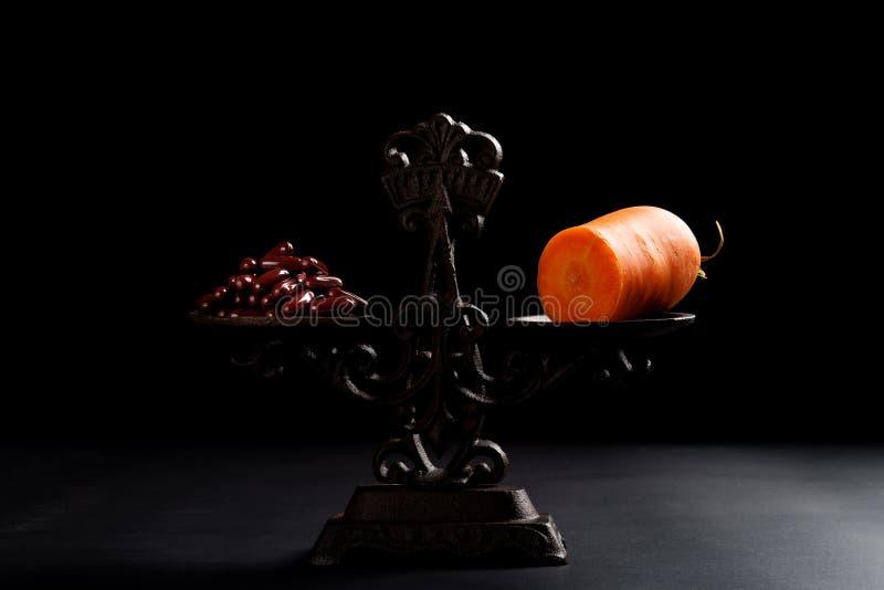 Δωδεκάδες των καψών και ενός καρότου σε μια ισορροπημένη έννοια κλίμακας της υγιούς κατανάλωσης στοκ εικόνες με δικαίωμα ελεύθερης χρήσης