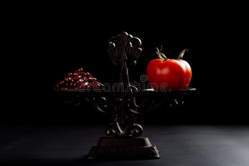 Δωδεκάδες των καψών και μιας ντομάτας σε μια ισορροπημένη κλίμακα στοκ εικόνες