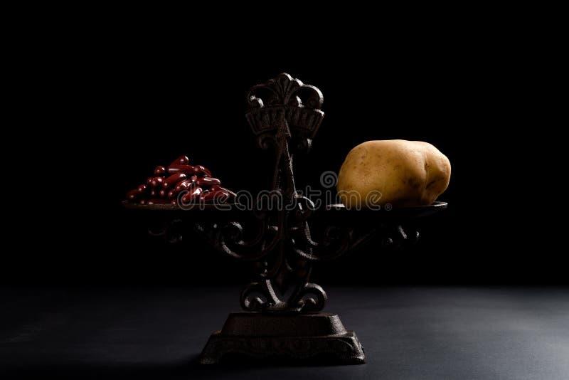 Δωδεκάδες των καψών και μιας πατάτας σε μια ισορροπημένη έννοια κλίμακας της υγιούς κατανάλωσης στοκ εικόνες