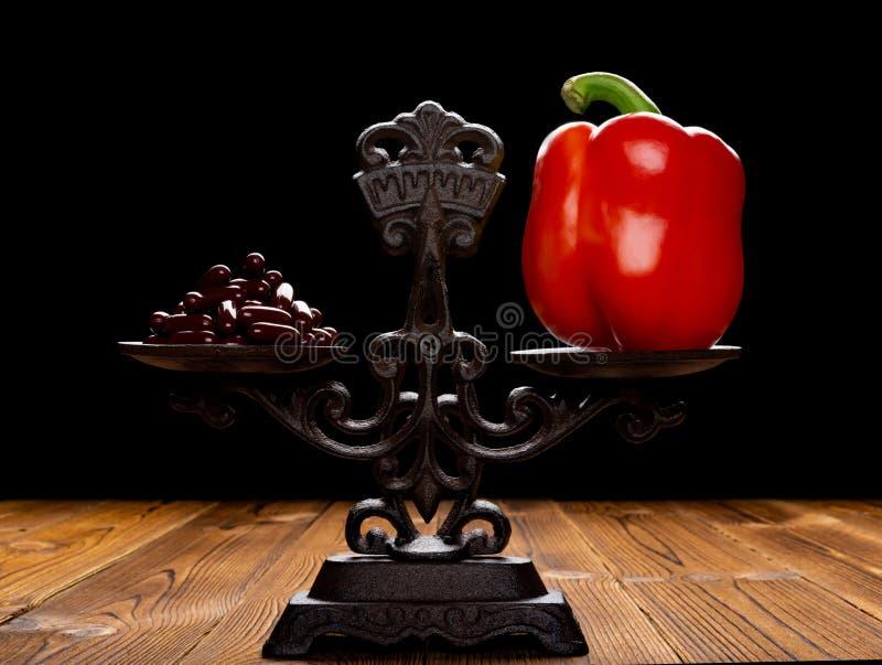 Δωδεκάδες των καψών και του κόκκινου πιπεριού κουδουνιών σε μια ισορροπημένη έννοια κλίμακας της υγιούς κατανάλωσης και του εναλλ στοκ φωτογραφία με δικαίωμα ελεύθερης χρήσης
