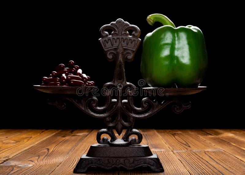 Δωδεκάδες των καψών και του πράσινου πιπεριού κουδουνιών σε μια ισορροπημένη έννοια κλίμακας της υγιούς κατανάλωσης και του εναλλ στοκ εικόνα