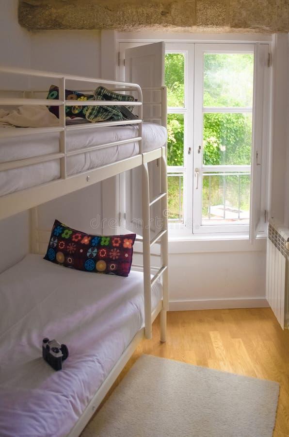 Δωμάτιο με το καθαρό κρεβάτι κουκετών ενάντια στο παράθυρο στοκ εικόνες