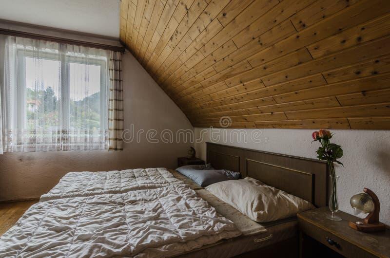 δωμάτιο με το κρεβάτι στη σοφίτα του παλαιού πανδοχείου στοκ φωτογραφίες