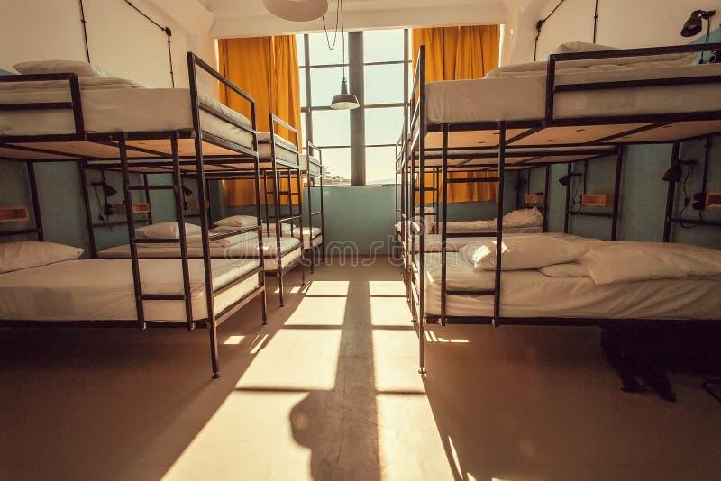 Δωμάτιο με το μεγάλο παράθυρο μέσα στον ξενώνα backpackers με τα σύγχρονα κρεβάτια κουκετών στοκ φωτογραφία