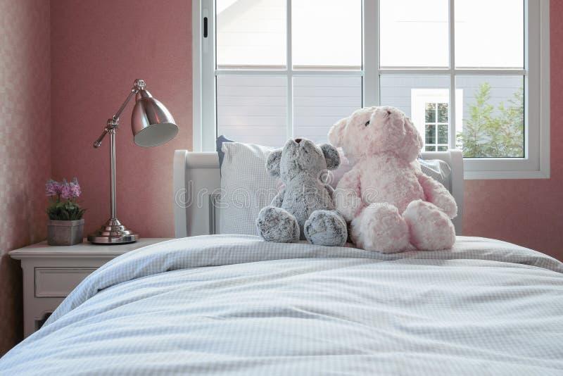 Δωμάτιο παιδιών με τις κούκλες και τα μαξιλάρια στον επιτραπέζιο λαμπτήρα κρεβατιών και πλευρών στοκ εικόνες