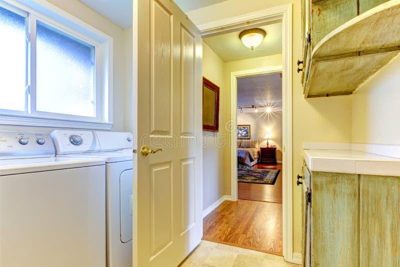 Δωμάτιο πλυντηρίων με τη ανοιχτή πόρτα στην κρεβατοκάμαρα. στοκ φωτογραφία με δικαίωμα ελεύθερης χρήσης