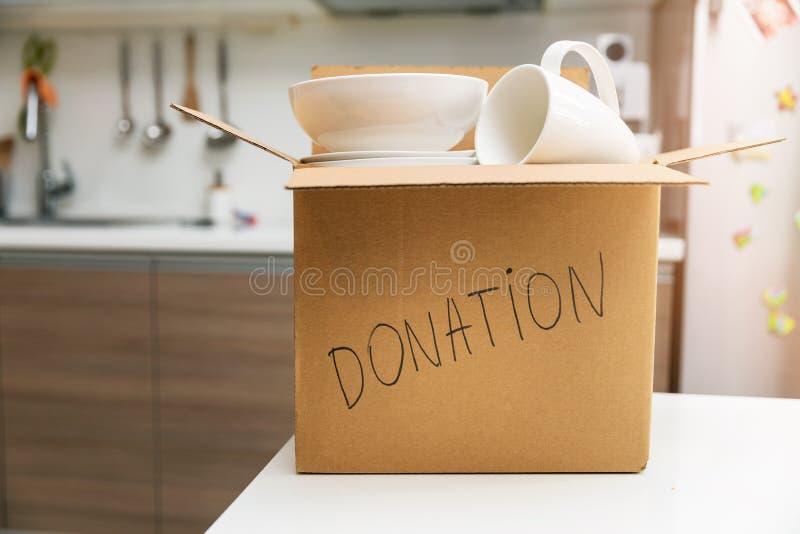 Δωρεά οικιακών ειδών - κουτί με επιτραπέζια σκεύη για δωρεά σε τραπέζι κουζίνας στοκ εικόνες